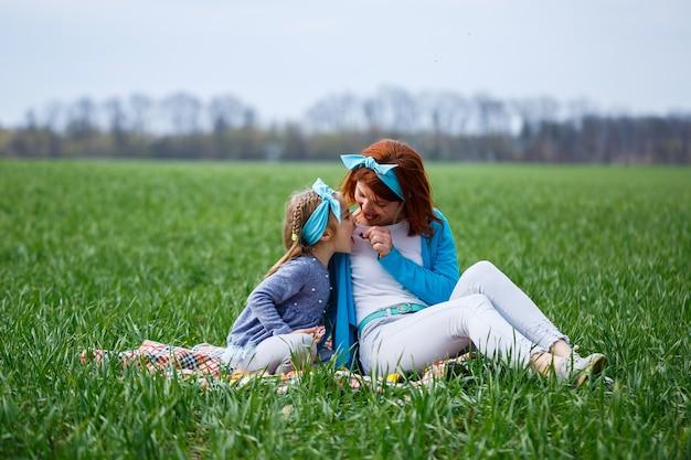 Mała dziewczynka dziecko i matka kobieta siedząca na narzucie i jedząca ciasteczka i marmoladę, zielona trawa na polu, słoneczna wiosenna pogoda, uśmiech i radość dziecka, błękitne niebo z chmurami