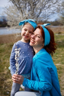 Mała dziewczynka dziecko i matka kobieta spaceruje po wiosennym lesie z kwitnącymi drzewami, śmieje się i bawi, początek wiosny, rodzinne wakacje, miłość rodziców