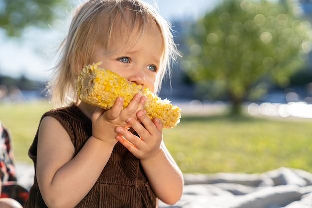 Mała dziewczynka dziecko jeść kolby kukurydzy, siedząc na kratę na trawie w letni dzień. zdrowe odżywianie.