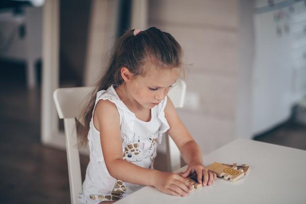 Mała dziewczynka dziecko ładny przedszkolak grając w gry edukacyjne z drewnianym
