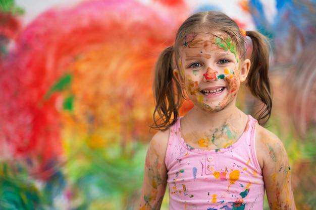 Mała dziewczynka dziecko przedszkolak rysuje ręce farby na białej ścianie.