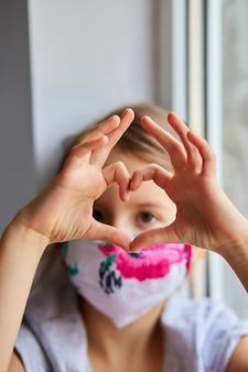 Mała dziewczynka, dziecko w masce robi serca z rąk, kwarantanna koronawirusa