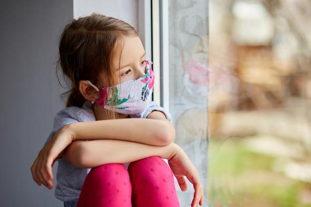 Mała dziewczynka, dziecko w masce siedzi na oknach, kwarantanna koronawirusa, domowa szkoła. zostań w domu. pojęcie kwarantanny koronawirusa.