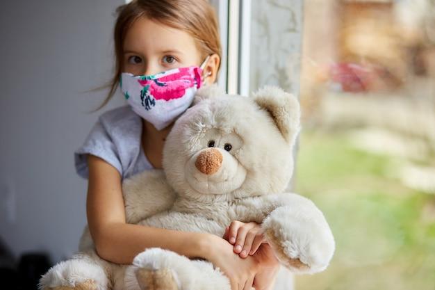 Mała dziewczynka, dziecko w masce z misiem siedzi na oknach, kwarantanna koronawirusa