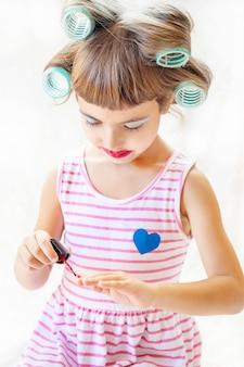 Mała dziewczynka. dziewczyna robi jej makijaż i manicure. selektywna ostrość.