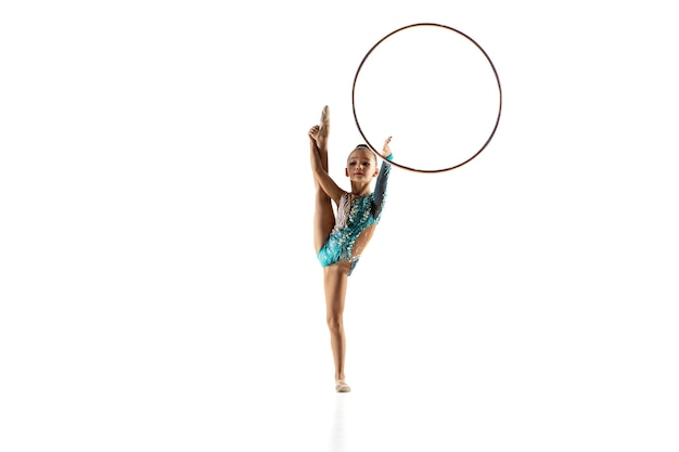 Mała dziewczynka elastyczna na białej ścianie. mała modelka jako artystka gimnastyki artystycznej w jasnym trykocie. wdzięk w ruchu, akcji i sporcie. wykonywanie ćwiczeń z obręczą.