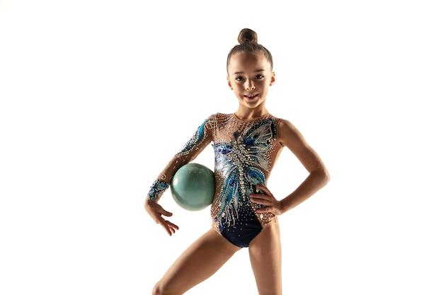 Mała dziewczynka elastyczna na białej ścianie. mała modelka jako artystka gimnastyki artystycznej w jasnym trykocie. wdzięk w ruchu, akcji i sporcie. wykonywanie ćwiczeń z piłką.