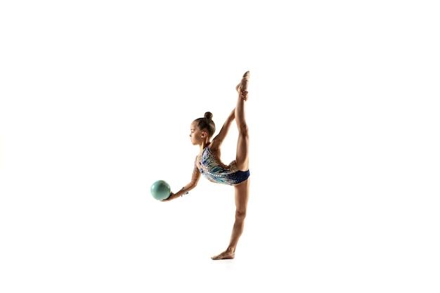 Mała dziewczynka elastyczna na białym tle na białej ścianie. mała modelka jako artystka gimnastyki artystycznej w jasnym trykocie. wdzięk w ruchu, akcji i sporcie. wykonywanie ćwiczeń z piłką.