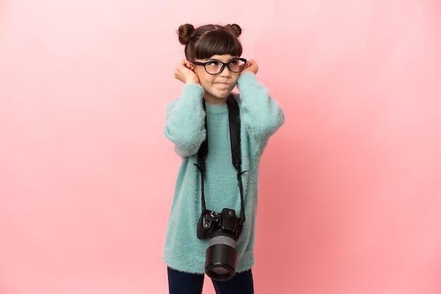 Mała dziewczynka fotograf na białym tle na różowym tle sfrustrowani i zakrywający uszy