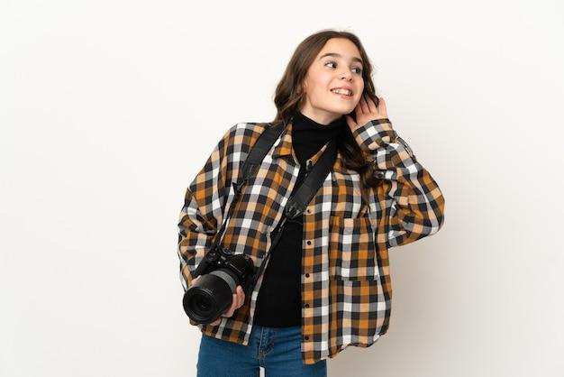 Mała dziewczynka fotograf na białym tle na tle słuchając czegoś, kładąc rękę na uchu