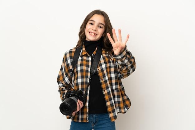 Mała dziewczynka fotograf na białym tle na tle szczęśliwy i licząc cztery palcami
