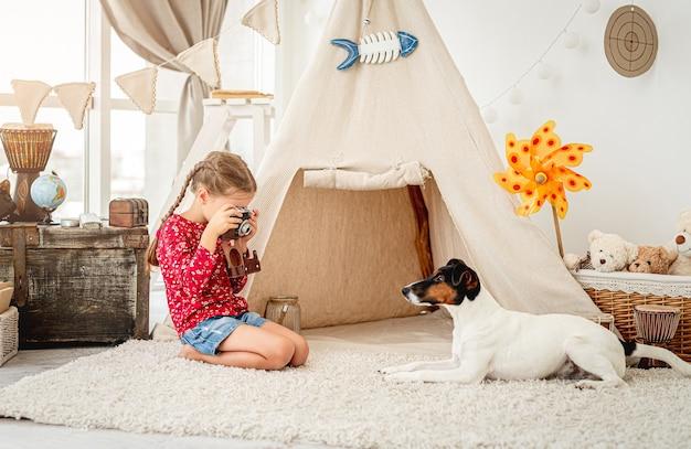 Mała dziewczynka fotografowanie foksterier psa z filmową kamerą w pomieszczeniu