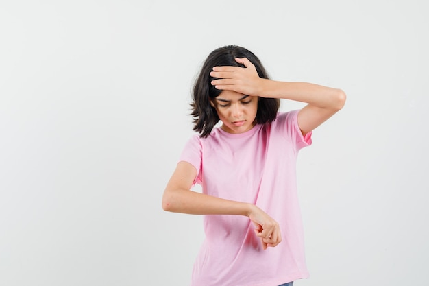 Mała dziewczynka gestykulująca, jakby patrzyła na zegarek na nadgarstku w różowym t-shircie i wyglądająca na zaniepokojoną, widok z przodu.