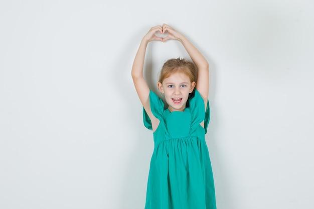 Mała dziewczynka gestykuluje kształt serca nad głową w zielonej sukni i wygląda wesoło. przedni widok.