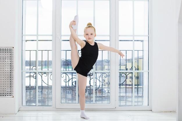 Mała dziewczynka gimnastyczka robi rozciąganie w jasnym pokoju na szczęśliwej i uroczej powierzchni okna