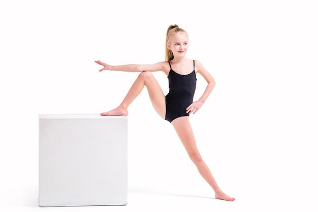 Mała dziewczynka gimnastyczka w czarnym stroju kąpielowym stojąc jedną nogą na białym sześcianie, na białym tle na białym tle