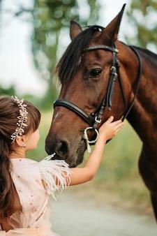 Mała dziewczynka głaszcze konia po głowie swojego ulubionego konia. komunikacja dziecka z koniem w lecie.