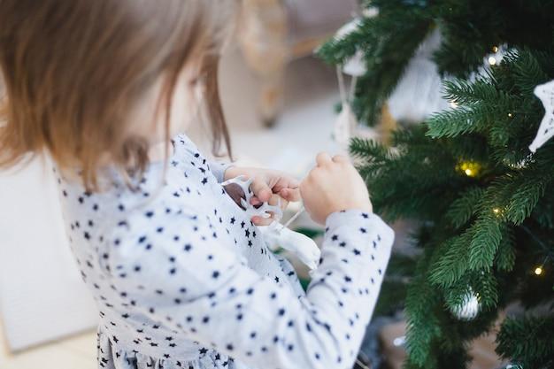 Mała dziewczynka gospodarstwa dekoracji na choinkę, wnętrze bożego narodzenia, przygotowanie do bożego narodzenia i nowego roku, dekoracja domu