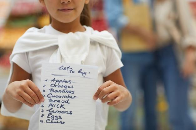 Mała dziewczynka gospodarstwa listy zakupów