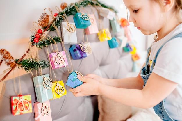 Mała dziewczynka gospodarstwa obecne pole ręcznie kalendarz adwentowy w domu. diy świąteczny kalendarz adwentowy dla dzieci