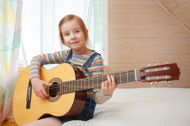 Mała dziewczynka gra na gitarze w domu.
