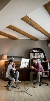 Mała dziewczynka gra na gitarze z nauczycielem muzyki w rustykalnym mieszkaniu