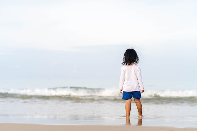 Mała dziewczynka gra na pięknym brzegu morza.