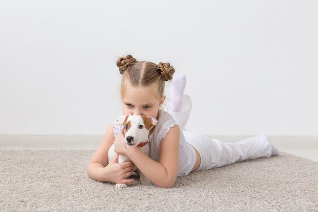 Mała dziewczynka gra na podłodze z szczeniakiem jackiem russellem