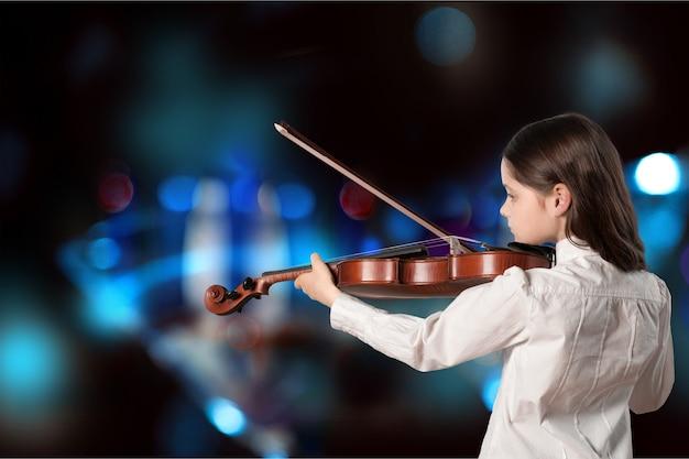 Mała dziewczynka gra na skrzypcach na rozmytym tle