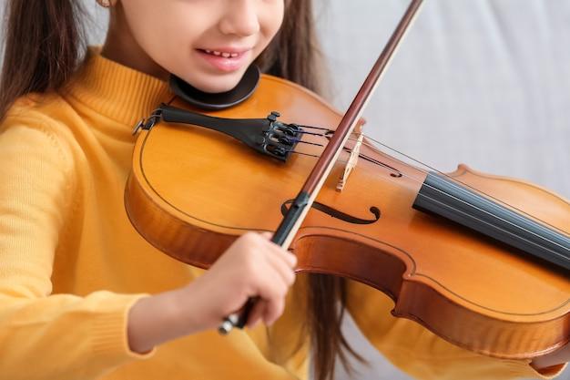 Mała dziewczynka gra na skrzypcach w domu, zbliżenie