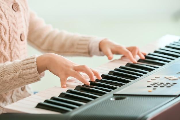 Mała dziewczynka gra na syntezatorze w domu, zbliżenie