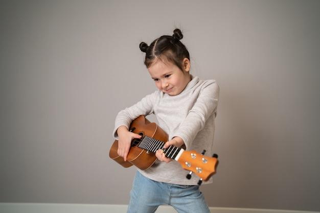 Mała dziewczynka gra na ukulele.