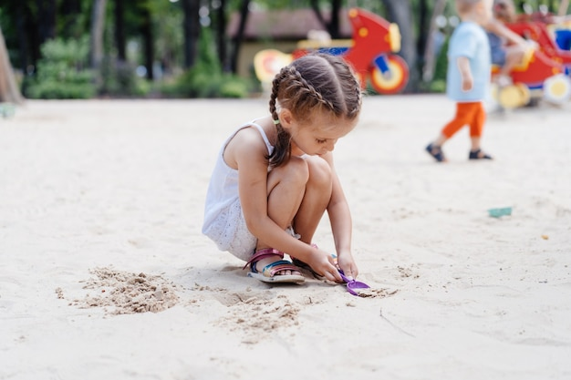 Mała dziewczynka gra plac zabaw dla dzieci w piaskownicy kopanie piasku łopata budynku piasek rysunek letni dzień. kaukaska kobieta dziecko 5 lat baw się na świeżym powietrzu