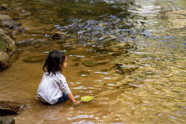 Mała dziewczynka gra przy wodospadzie podczas letnich wakacji