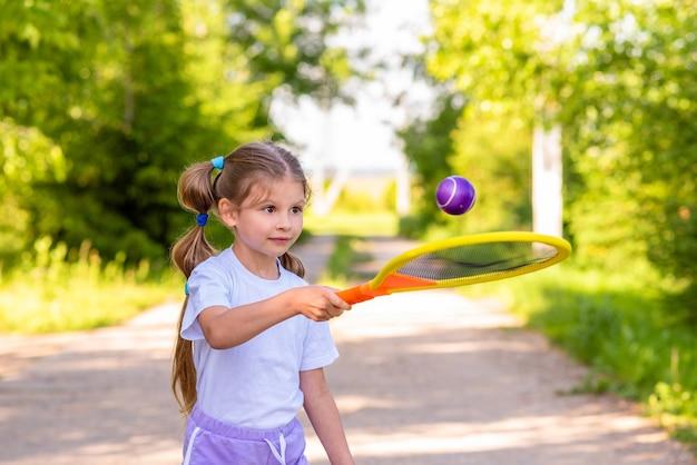 Mała dziewczynka gra rakietą tenisową i piłką.