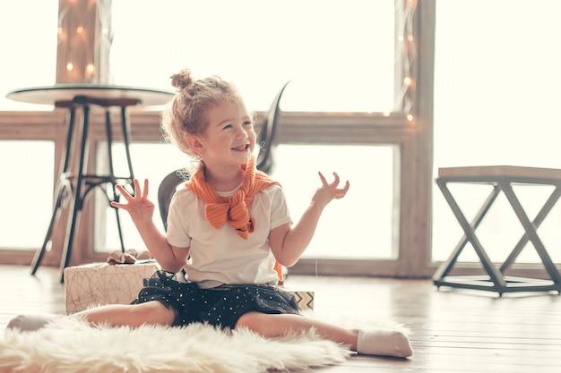 Mała dziewczynka gra siedząc na dywanie w salonie. koncepcja szczęśliwego dzieciństwa