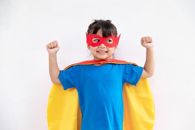 Mała dziewczynka gra superbohatera. dziecko na białym tle. koncepcja mocy dziewczyny