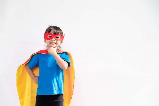 Mała Dziewczynka Gra Superbohatera. Dziecko Na Białym Tle. Koncepcja Mocy Dziewczyny Premium Zdjęcia