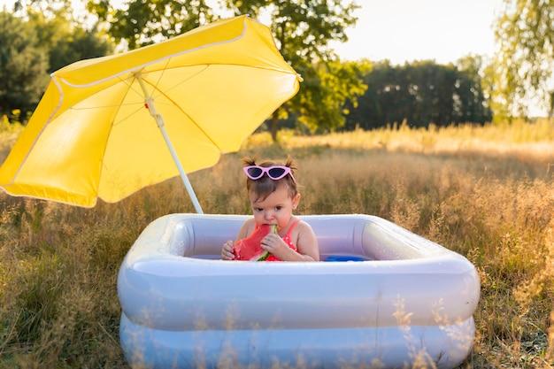 Mała dziewczynka gra w nadmuchiwanym basenie.