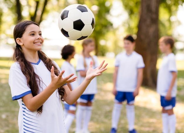 Mała dziewczynka gra w piłkę nożną na zewnątrz