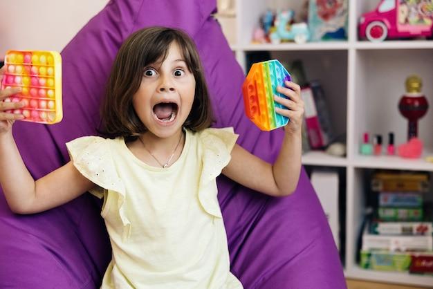 Mała dziewczynka gra w pop to prostą zabawkę z dołeczkiem, kolorową i jasną zabawką pop it