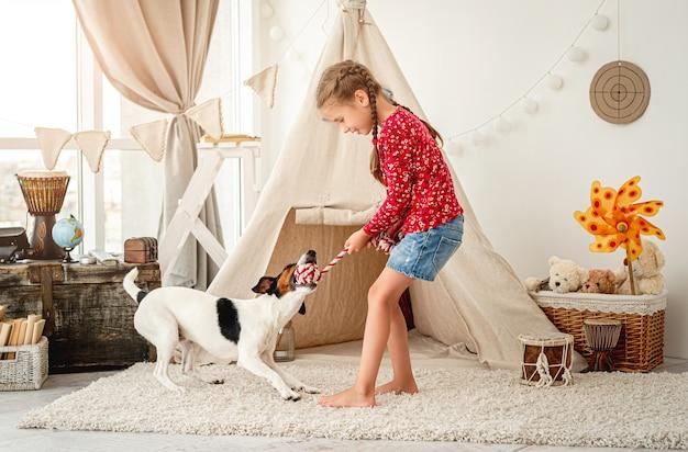 Mała dziewczynka gra z gładkim foksterierem w pokoju dziecięcym