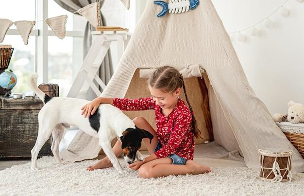Mała dziewczynka gra z gładkim psem foksterier w domu