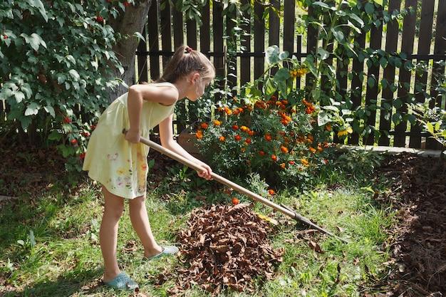 Mała dziewczynka grabie suche liście w ogrodzie na tle kwiatów