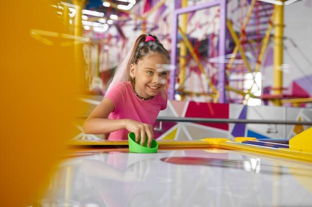 Mała dziewczynka grać w cymbergaja w centrum rozrywki. zabawa dzieci, rywalizacja sportowa na placu zabaw, szczęśliwe dzieciństwo
