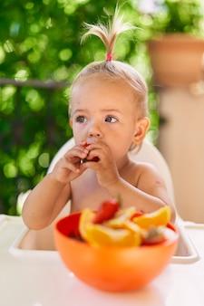 Mała dziewczynka gryzie truskawkę, trzymając ją za ręce