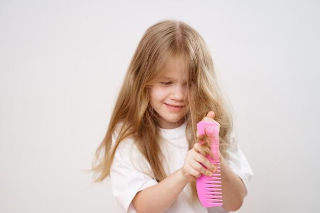 Mała dziewczynka grzebie długie włosy na białym tle. kosmetyki do pielęgnacji włosów dziecięcych.
