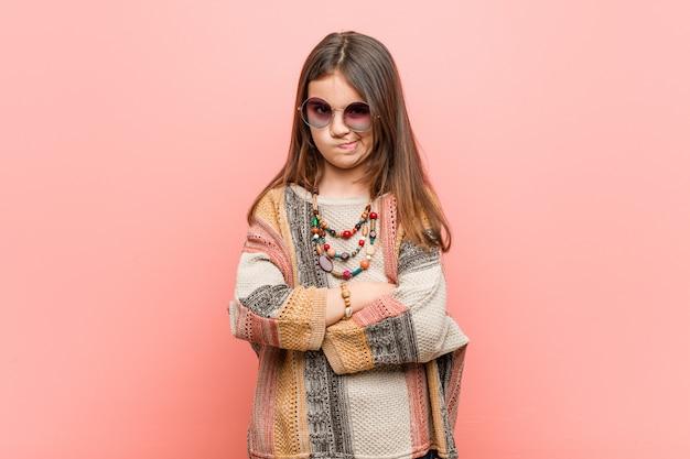 Mała dziewczynka hipis marszczy brwi z niezadowolenia, trzyma ręce złożone.
