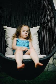Mała dziewczynka huśtająca się w wiszącym fotelu. dziecko ma blond włosy. mała dziewczynka na huśtawce z rattanem