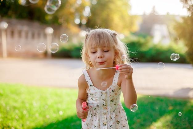 Mała dziewczynka i baniek mydlanych w parku